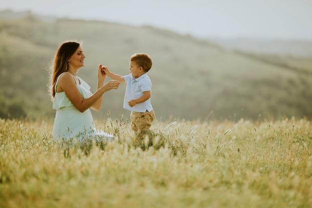 Młoda ciężarna matka z jej ślicznym chłopiec w polu na pięknym słonecznym dniu
