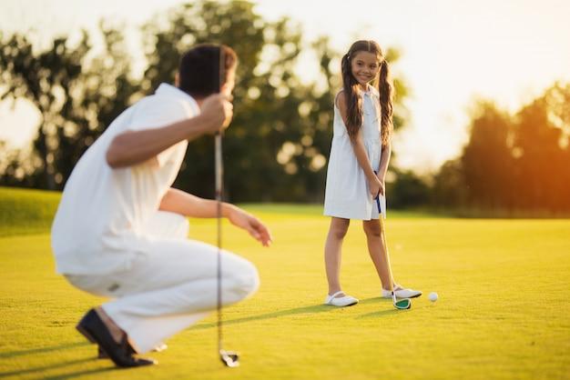 Młoda córka bierze golfa szczęśliwa rodzina.