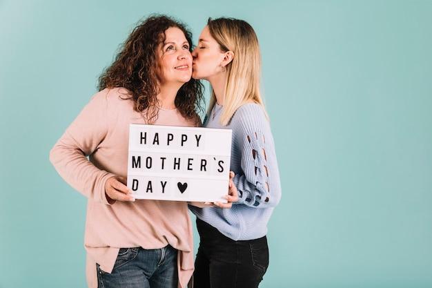Młoda córka całuje mamę na dzień matki