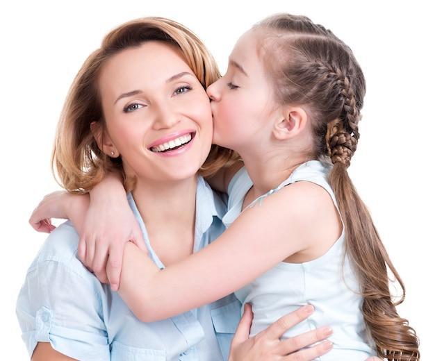 Młoda córka całuje matkę - na białym tle