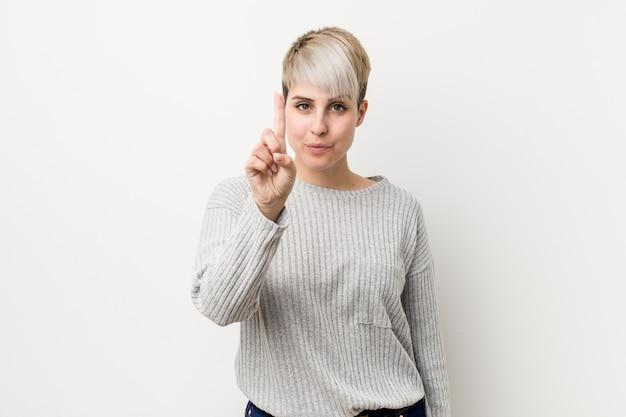 Młoda curvy caucasian kobieta odizolowywająca na biel ścianie pokazuje liczbę jeden z palcem.