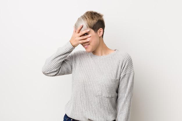 Młoda curvy caucasian kobieta odizolowywająca na bielu mruga przy kamerą przez palców