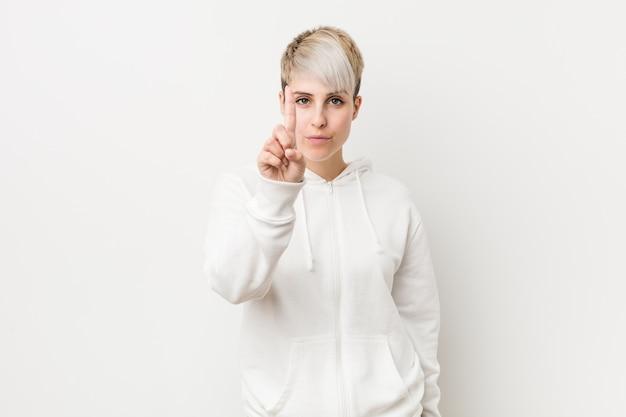 Młoda curvy kobieta jest ubranym białą bluza z kapturem pokazuje liczbę jeden z palcem.