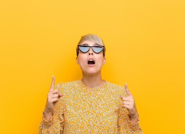 Młoda curvy kobieta jest ubranym kwiecistego lato odziewa wskazywać do góry z rozpieczętowanym usta.