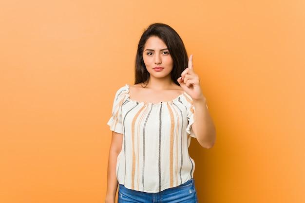 Młoda curvy kobieta pokazuje liczbę jeden z palcem.