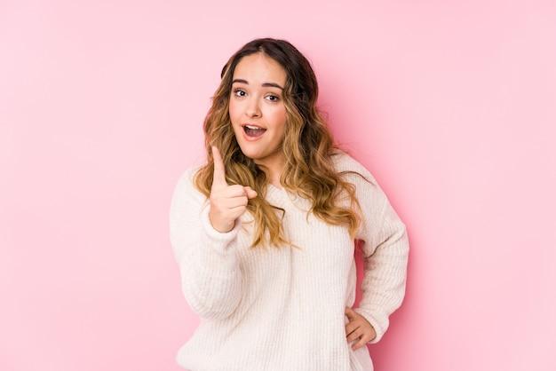 Młoda curvy kobieta pozuje w różowej ścianie odizolowywającej mieć pomysł, inspiraci pojęcie.