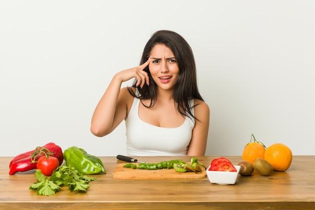 Młoda curvy kobieta przygotowywa zdrowego posiłek pokazuje rozczarowanie gest z palcem wskazującym.