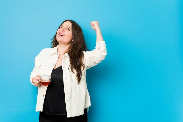 Młoda curvy kobieta trzyma herbacianej filiżanki dźwigania pięść po zwycięstwa, zwycięzcy pojęcie.