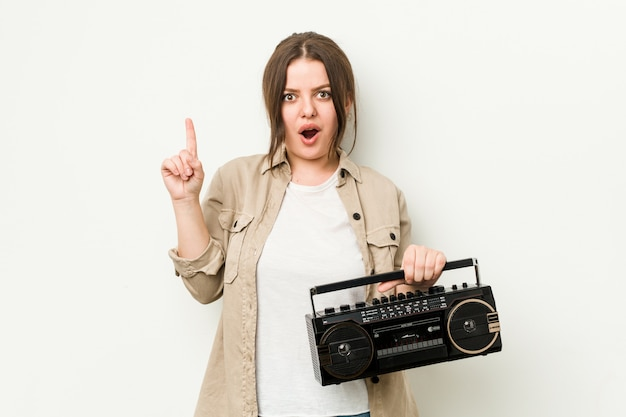 Młoda curvy kobieta trzyma retro radio ma niektóre doskonałego pomysł, pojęcie twórczość.