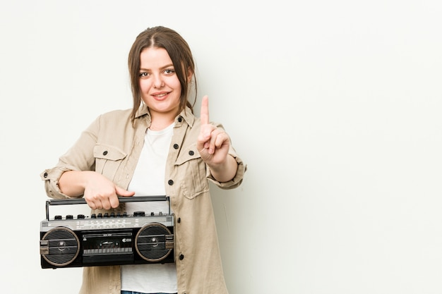 Młoda curvy kobieta trzyma retro radio pokazuje liczbę jeden z palcem.