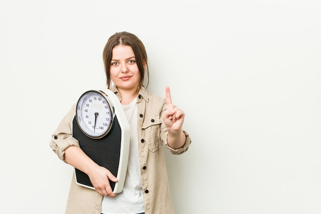 Młoda curvy kobieta trzyma skala pokazuje liczbę jeden z palcem.