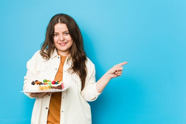Młoda curvy kobieta trzyma słodkich torty ono uśmiecha się i wskazuje na boku, pokazuje coś przy pustą przestrzenią.