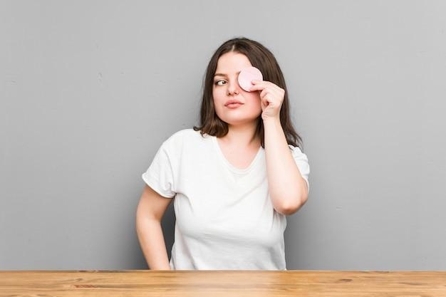 Młoda curvy kobieta trzyma twarzowego dyska odizolowywający na szarej ścianie