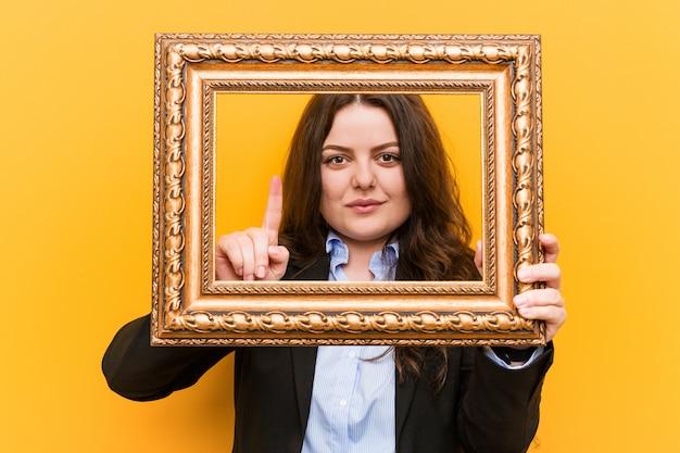 Młoda curvy plus wielkościowa biznesowa kobieta trzyma ramę pokazuje liczbę jeden z palcem.