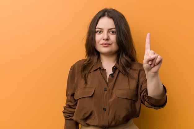 Młoda curvy rosyjska kobieta pokazuje liczbę jeden z palcem.