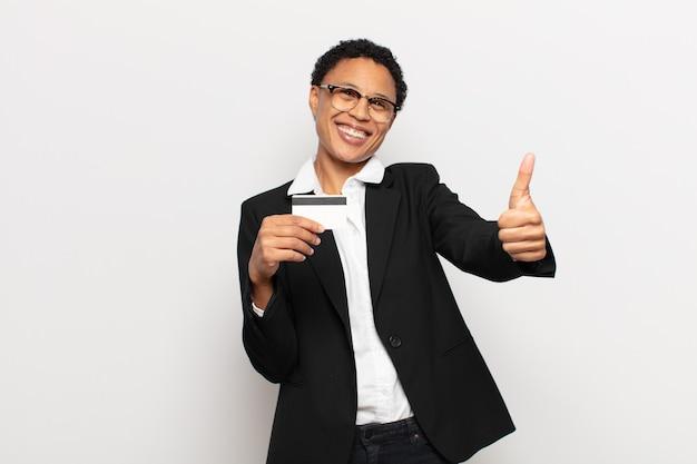 Młoda czarna afro kobieta czująca się dumna, beztroska, pewna siebie i szczęśliwa, uśmiechająca się pozytywnie z kciukami do góry