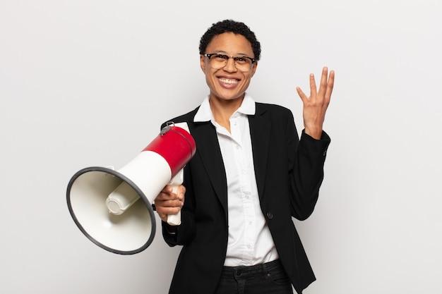 Młoda czarna afro kobieta czująca się szczęśliwa, zdziwiona i wesoła, uśmiechnięta pozytywnie, realizująca rozwiązanie lub pomysł