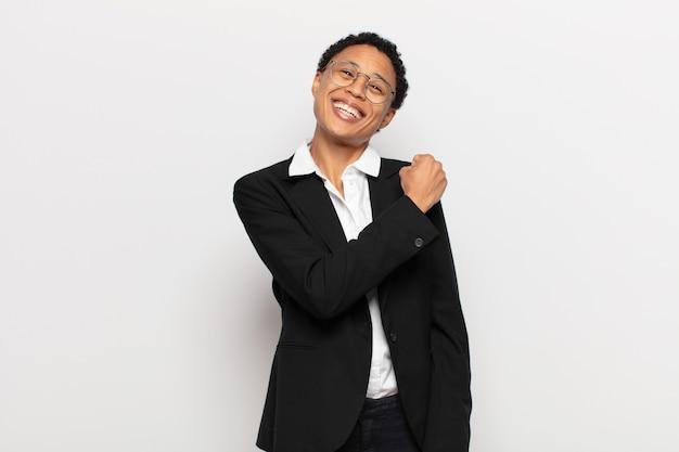 Młoda czarna afro kobieta czuje się szczęśliwa, pozytywna i odnosząca sukcesy, zmotywowana, gdy staje przed wyzwaniem lub świętuje dobre wyniki
