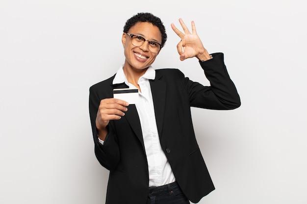 Młoda czarna afro kobieta czuje się szczęśliwa, zrelaksowana i usatysfakcjonowana, pokazując aprobatę z dobrym gestem, uśmiechając się