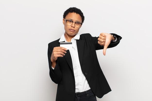 Młoda czarna afro kobieta czuje się zła, zła, zirytowana, rozczarowana lub niezadowolona, pokazując kciuki w dół z poważnym spojrzeniem