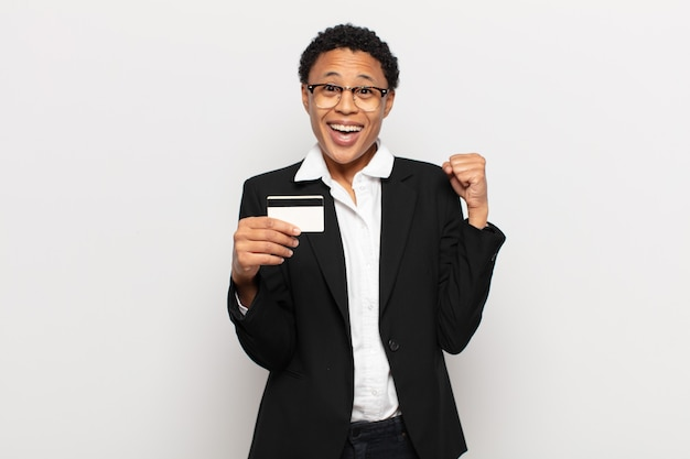 Młoda czarna afro kobieta czuje się zszokowana, podekscytowana i szczęśliwa, śmiejąca się i świętująca sukces, mówiąca wow!