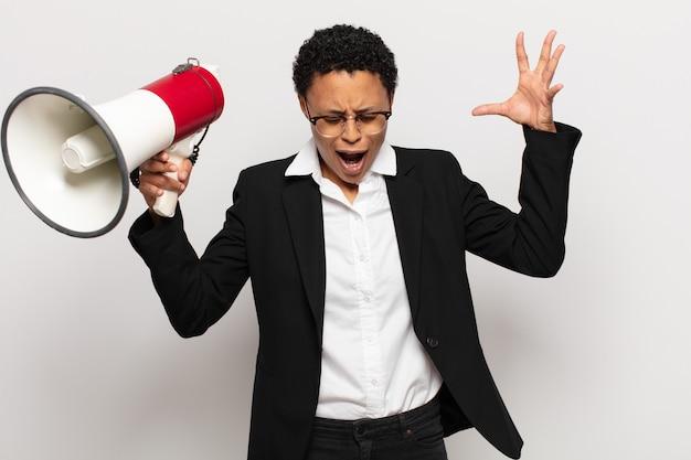 Młoda czarna afro kobieta krzyczy z rękami do góry, czuje się wściekła, sfrustrowana, zestresowana i zdenerwowana