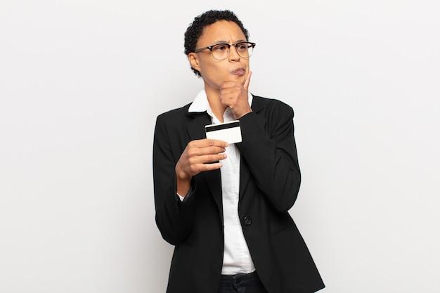Młoda czarna afro kobieta myśli, czuje się niepewna i zdezorientowana, ma różne opcje, zastanawia się, jaką decyzję podjąć