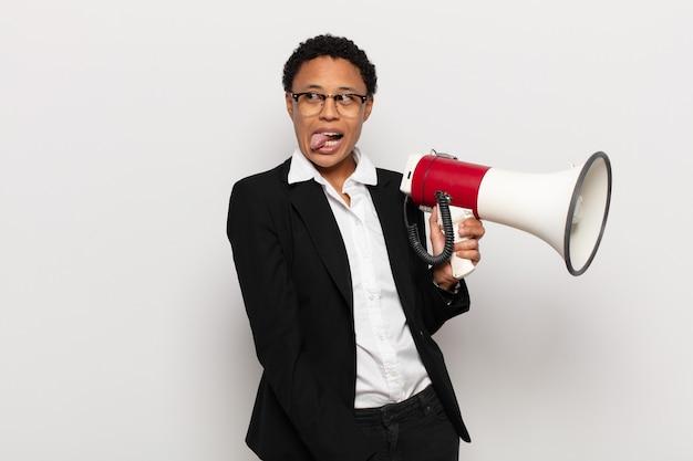 Młoda czarna afro kobieta o wesołej, beztroskiej, buntowniczej postawie, żartującej i wystawiającej język, dobrze się bawiąc