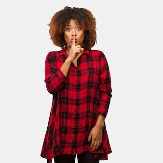 Młoda czarna afro kobieta trzymająca sekret lub prosząca o ciszę