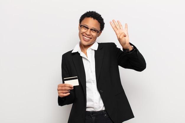 Młoda czarna afro kobieta uśmiecha się i wygląda przyjaźnie, pokazując numer cztery lub czwarty z ręką do przodu, odliczając w dół