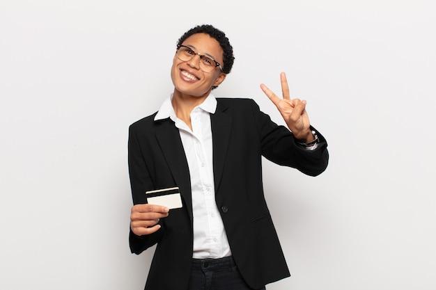 Młoda czarna afro kobieta uśmiecha się i wygląda przyjaźnie, pokazując numer dwa lub sekundę z ręką do przodu, odliczając w dół