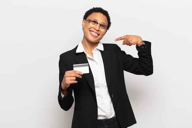 Młoda czarna afro kobieta uśmiecha się pewnie, wskazując na swój szeroki uśmiech, pozytywne, zrelaksowane, zadowolone nastawienie