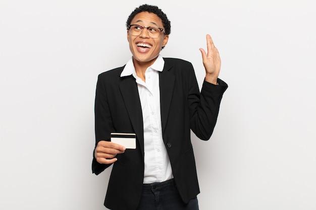 Młoda czarna afro kobieta uśmiecha się radośnie i wesoło, macha ręką, wita i wita lub żegna się