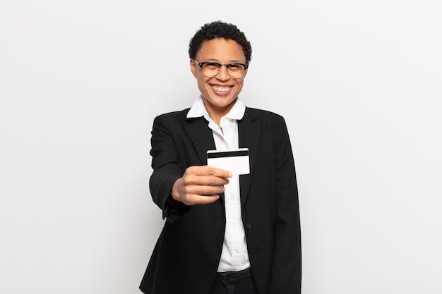 Młoda czarna afro kobieta uśmiecha się radośnie z przyjaznym, pewnym siebie, pozytywnym spojrzeniem, oferuje i pokazuje przedmiot lub koncepcję