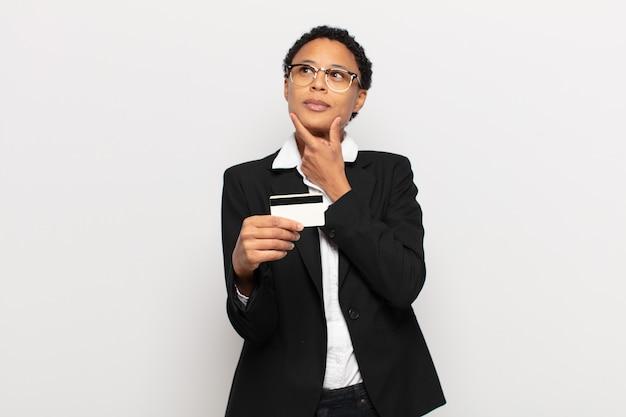 Młoda czarna afro kobieta uśmiecha się z radosnym, pewnym siebie wyrazem z ręką na brodzie, zastanawia się i patrzy w bok