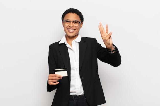Młoda czarna afro kobieta uśmiechnięta i wyglądająca przyjaźnie, pokazująca numer trzy lub trzeci z ręką do przodu, odliczający