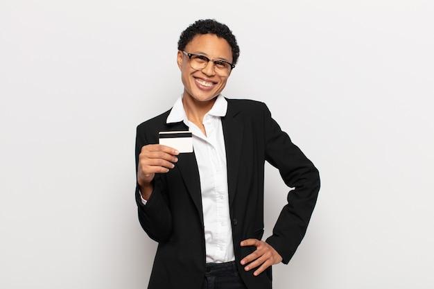 Młoda czarna afro kobieta uśmiechnięta radośnie z ręką na biodrze i pewną siebie, pozytywną, dumną i przyjazną postawą