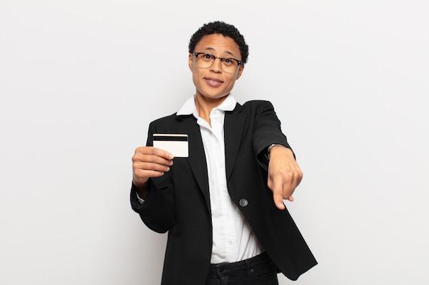 Młoda czarna afro kobieta wskazując na aparat z zadowolonym, pewnym siebie, przyjaznym uśmiechem, wybiera cię
