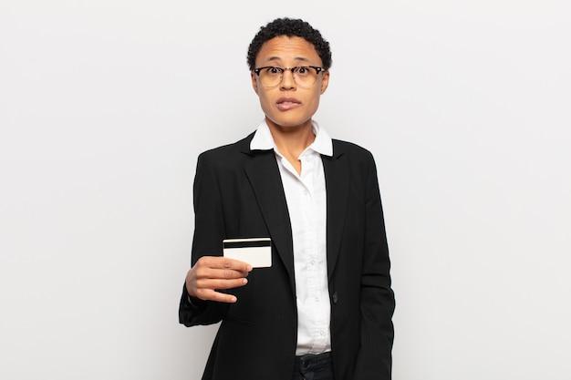Młoda czarna afro kobieta wyglądająca na zaskoczoną i zdezorientowaną, przygryzając wargę nerwowym gestem, nie znając odpowiedzi na problem