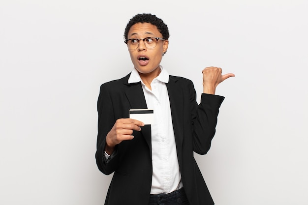 Młoda czarna afro kobieta wyglądająca na zaskoczoną z niedowierzaniem, wskazująca na przedmiot z boku i mówiąca wow, niewiarygodne