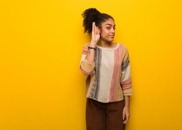 Młoda czarna afroamerykanka o niebieskich oczach próbuje słuchać plotek
