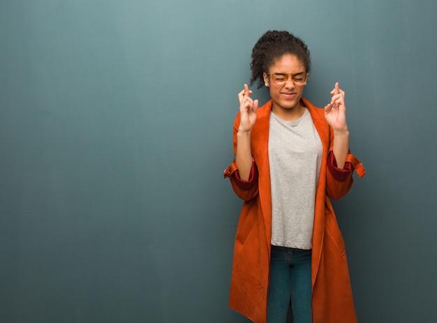 Młoda czarna amerykanin afrykańskiego pochodzenia dziewczyna krzyżuje palce z niebieskimi oczami dla mieć szczęście