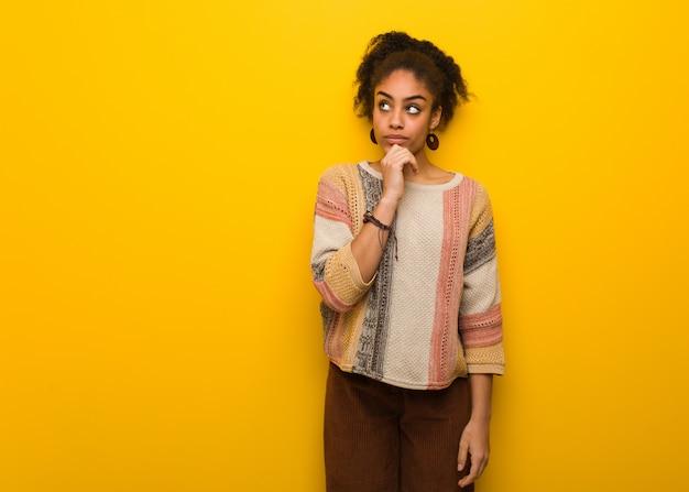 Młoda czarna amerykanin afrykańskiego pochodzenia dziewczyna myśleć o pomysle z niebieskimi oczami