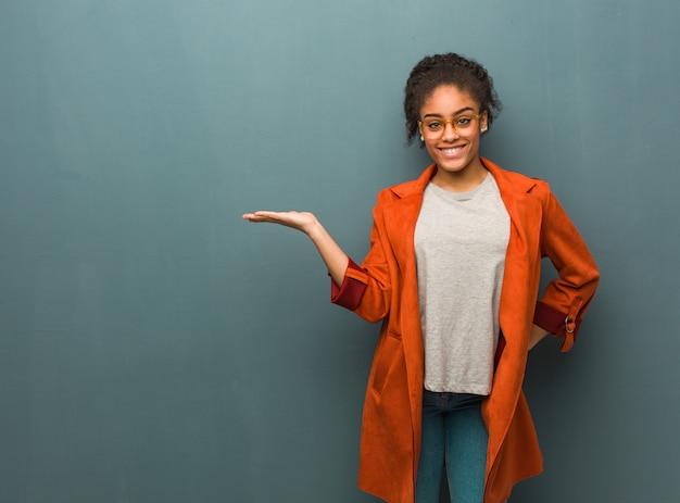 Młoda czarna amerykanin afrykańskiego pochodzenia dziewczyna trzyma coś z ręką o niebieskich oczach