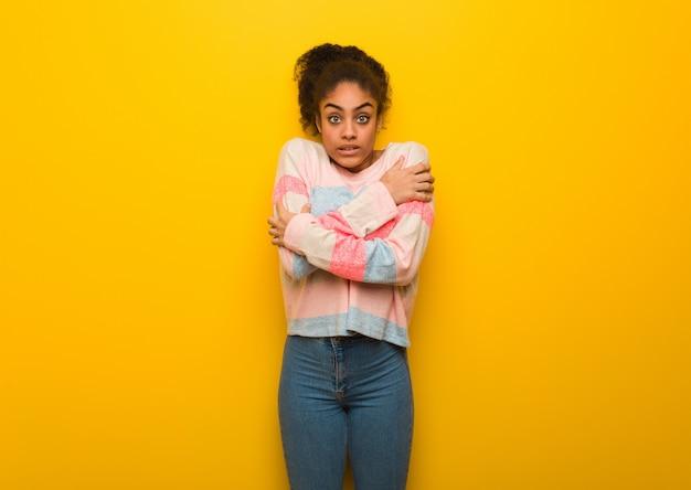 Młoda czarna amerykanin afrykańskiego pochodzenia dziewczyna z niebieskimi oczami iść zimno z powodu niskiej temperatury