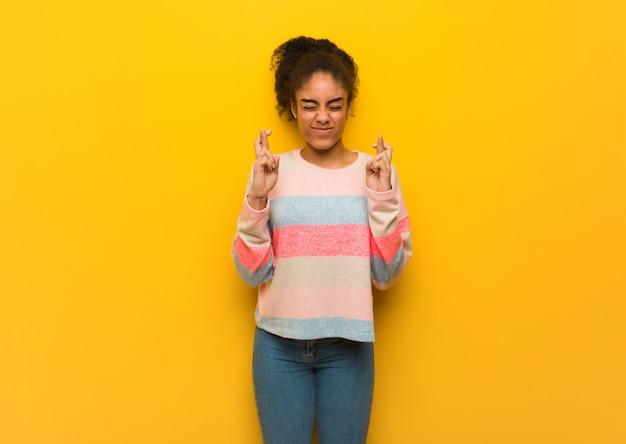 Młoda czarna amerykanin afrykańskiego pochodzenia dziewczyna z niebieskimi oczami krzyżuje palce dla mieć szczęście