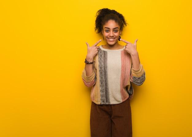 Młoda czarna amerykanin afrykańskiego pochodzenia dziewczyna z niebieskimi oczami ono uśmiecha się, wskazuje usta