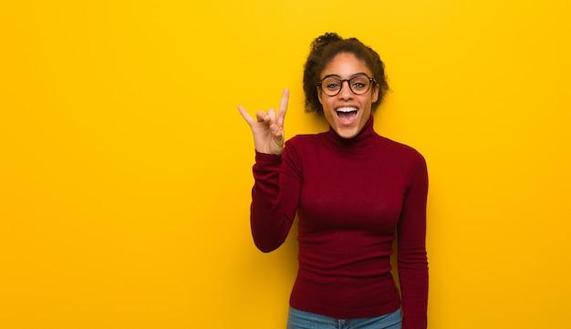 Młoda czarna amerykanin afrykańskiego pochodzenia dziewczyna z niebieskimi oczami robi rockowemu gestowi