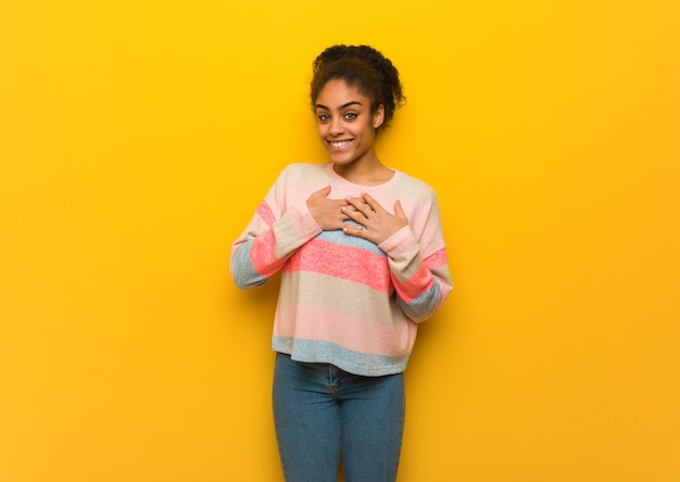 Młoda czarna amerykanin afrykańskiego pochodzenia dziewczyna z niebieskimi oczami robi romantycznemu gestowi