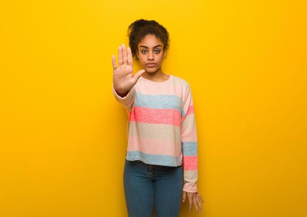 Młoda czarna amerykanin afrykańskiego pochodzenia dziewczyna z niebieskimi oczami stawia rękę w przodzie